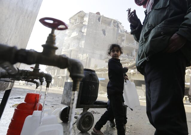 This file photo taken on January 21, 2017 shows Syrians standing next to water faucets as they fill jerrycans in Aleppo's formerly rebel-held al-Shaar neighbourhood, a month after government forces retook the northern Syrian city from rebel fighters
