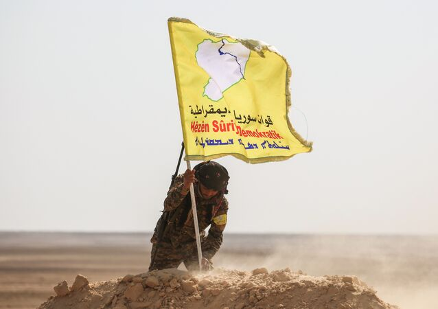 A member of the Syrian Democratic Forces (SDF), made up of US-backed Kurdish and Arab fighters, raises a flag of the SDF near the village of Bir Fawaz, 20 km north of Raqqa, during their offensive towards the Islamic State (IS) group's Syrian stronghold as part of the third phase retake the city and its surroundings, on February 8, 2017