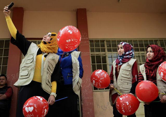 Members from the Rebirth Generation, an internet born group of Iraqi youths who are trying to revive the embattled city of Mosul, pose for a photo as they organise an event to mark Valentine's Day at a school in the eastern part of Mosul on February 14, 2017