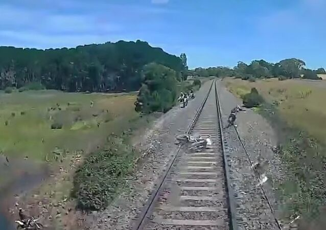 Motorbike rider narrowly misses being hit by high speed train news