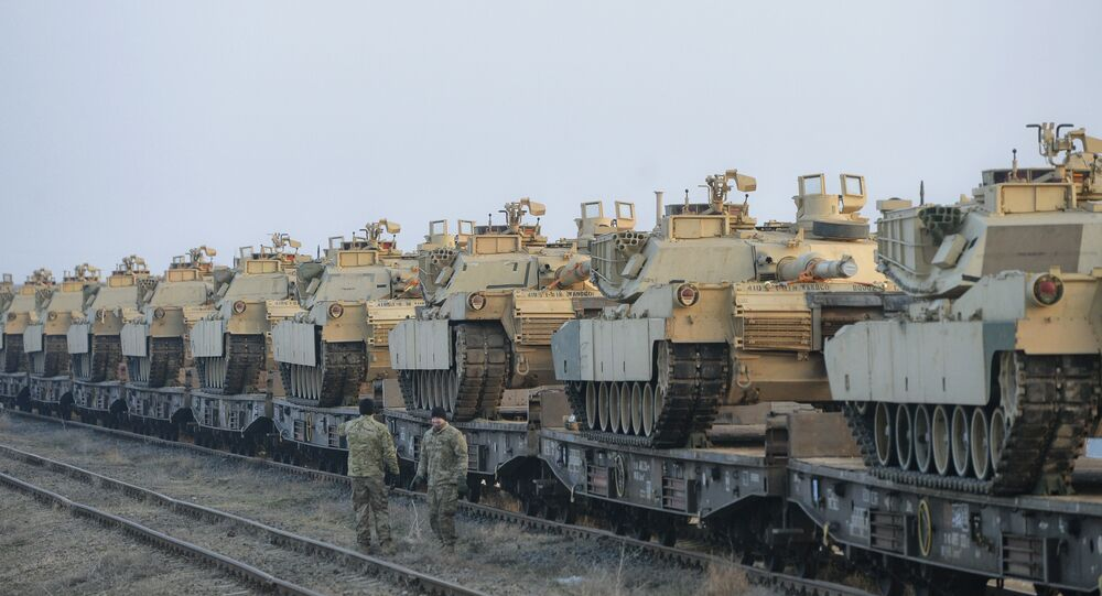 Servicemen of the Fighting Eagles 1st Battalion, 8th Infantry Regiment, walk by tanks that arrived via train to the US base in Mihail Kogalniceanu, eastern Romania, Tuesday, Feb. 14, 2017.