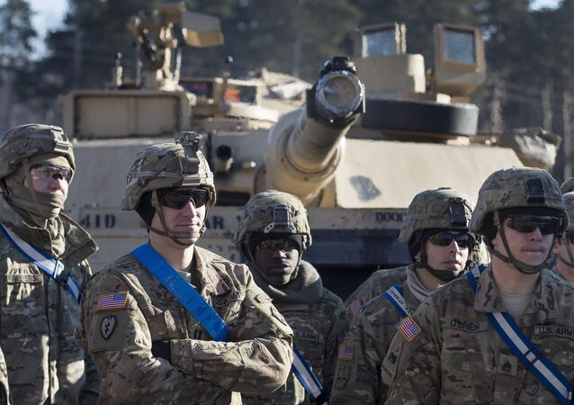 Members of US Army's 4th Infantry Division 3rd Brigade Combat Team 68th Armor Regiment 1st Battalion stand in front of an Abrams battle tank after arriving at the Gaiziunai railway station, some 110 kms (69 miles) west of the capital Vilnius, Lithuania, Friday, Feb. 10, 2017.
