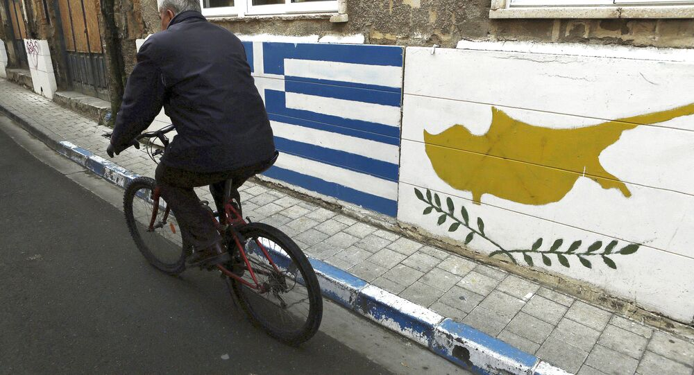 A man passes with a bicycle outside of a Greek Cypriot guard post with Cyprus', right, and Greece' flags painted on the wall in central divided capital Nicosia in the eastern Mediterranean island of Cyprus, on Thursday, Feb. 16, 2017.
