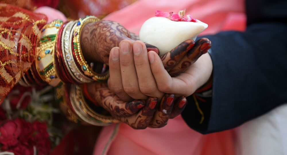 An Indian couple prepares to take part in a mass wedding in Ahmedabad