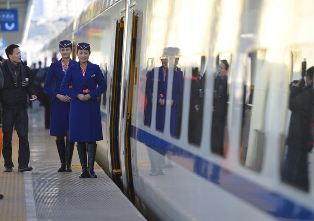 Train conductors stand outside the cabin of a bullet train