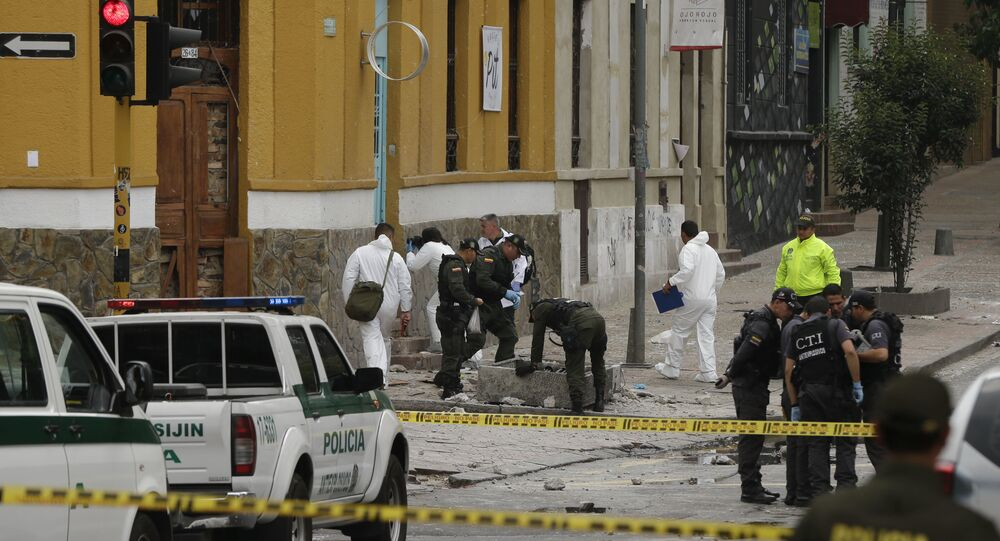 Police and investigators inspect the site where a homemade bomb exploded near the Santamaria bull ring in Bogota, Colombia