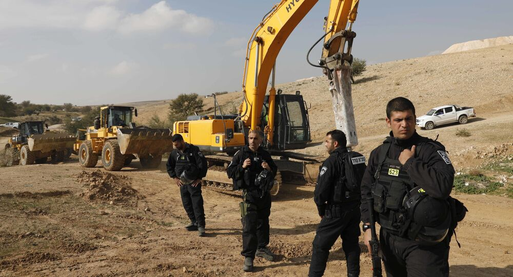 Israeli policemen stand guard next to bulldozers (File)