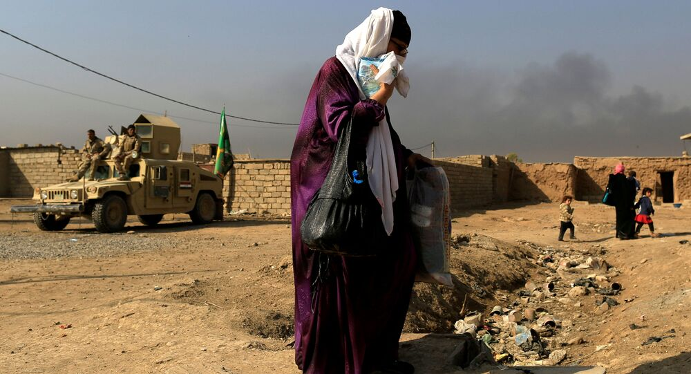 A woman who is fleeing the fighting between Islamic State and the Iraqi army in the Intisar district of eastern Mosul, walks past a military humvee while heading to safer territory in Iraq November 7, 2016.