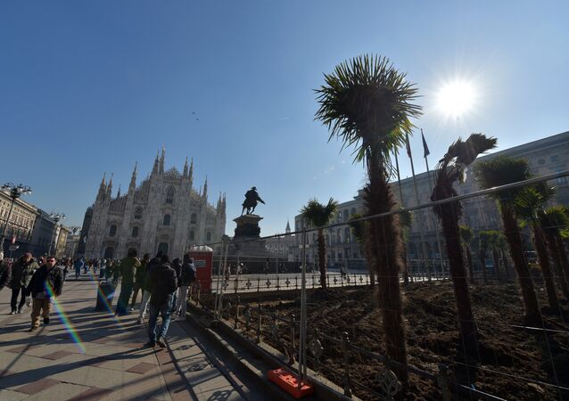 People walk past newly planted palm trees in an area near Italy's landmark, the Milan Cathedral, at the Piazza del Duomo in Milan on February 16, 2017