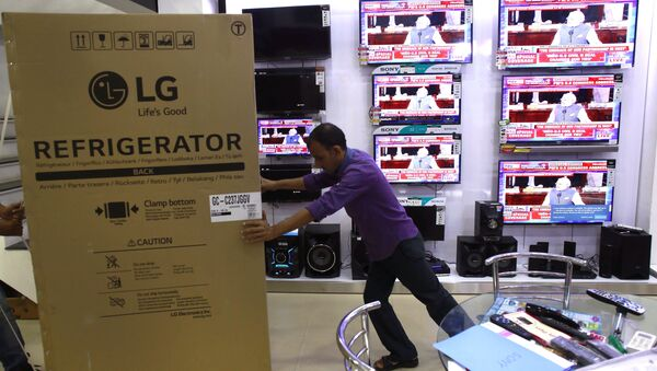 An Indian worker pushes a refrigerator to its place, as Indian Prime Minister Narendra Modi addresses a joint meeting of Congress on Capitol Hill in Washington seen on televisions at an electronic shop, in Gauhati, India , Wednesday, June 8, 2016 - Sputnik International