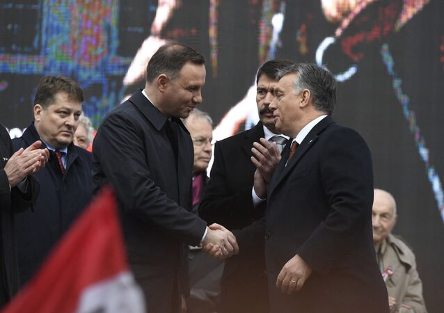Polish President Andrzej Duda, center left, is welcomed by Hungarian Prime Minister Viktor Orban on the podium as Hungarian President Janos Ader, second right, and Speaker of the Hungarian Parliament Laszlo Kover, left, applaud during the state commemoration ceremony of the 1956 Hungarian revolution and freedom fight against communism and Soviet rule in front of the Parliament building in downtown Budapest, Hungary, Sunday, Oct. 23, 2016