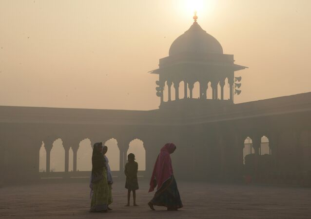 This file photo taken on November 3, 2016 shows Indian women walking as smog envelops the Jama Masjid mosque in the old quarters of New Delhi