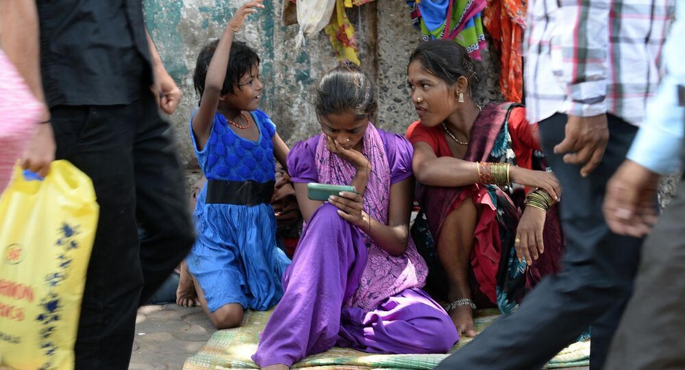 An Indian pavement dweller watches a movie on a mobile phone as others interact in Mumbai on June 3, 2015