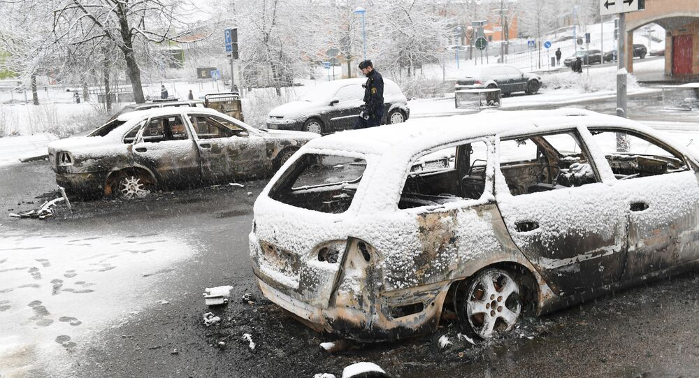 A policeman investigates a burnt car in the Rinkeby suburb outside Stockholm, Sweden.