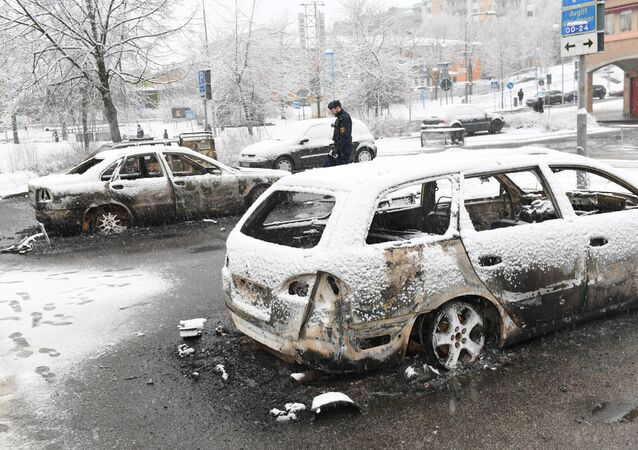 A policeman investigates a burnt car in the Rinkeby suburb outside Stockholm, Sweden February 21, 2017