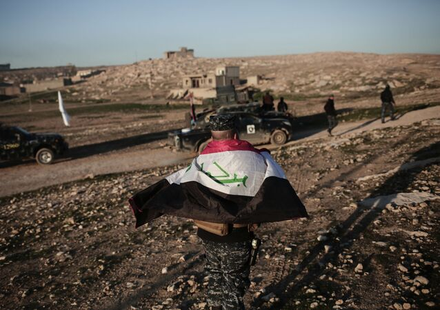 A member of the Iraqi federal police wears an Iraqi flag around his shoulders before going to battle against the Islamic State group