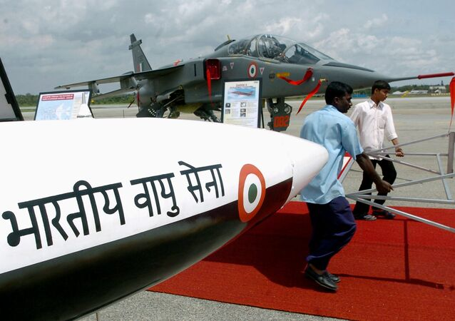 Workers of the Hindustan Aeronautics Limited (HAL) walk past a Lakshya (unmanned aerial vehicle) carrying a display board as Jaguar aircraft are on display at theHindustan Aeronautics Limited (HAL) airport in Bangalore