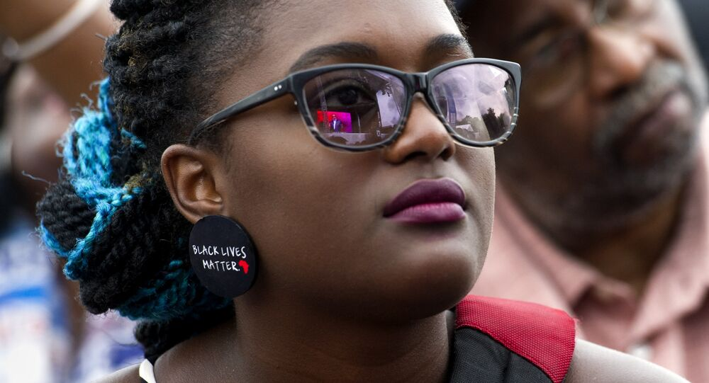A young woman wears earrings with the slogan Black Lives Matter printed on them during the dedication and opening ceremony of the Smithsonian's National Museum of African American History and Culture in Washington, Saturday, Sept. 24, 2016.