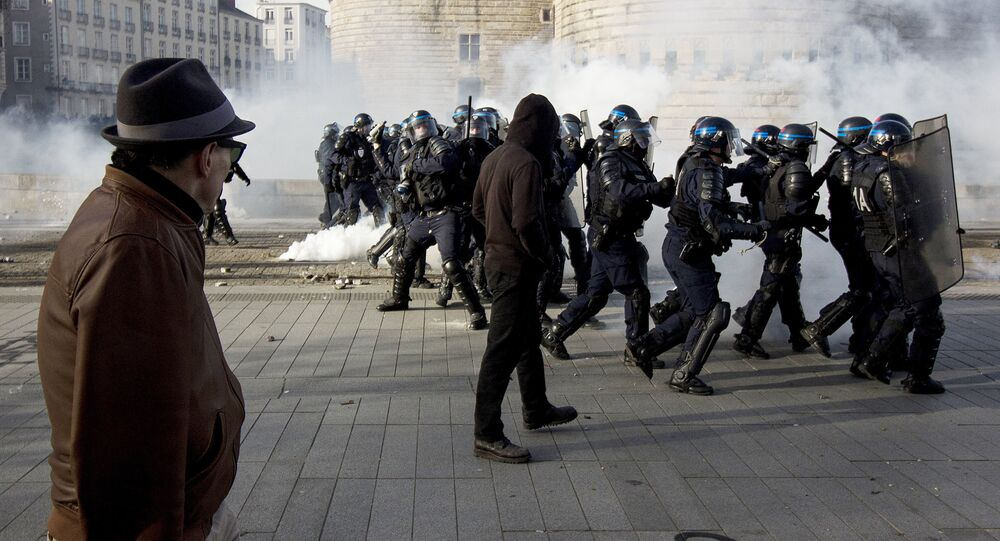 A man looks at riot police throwing tear gas while protesters demonstrate against the visit of French presidential election candidate for the far-right Front National (FN) party, on February 25, 2017 in Nantes, western France.