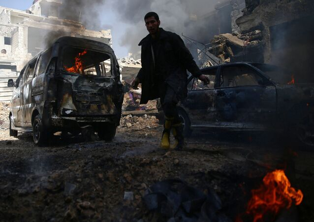 A civil defence member works amid burning vehicles at a site hit by airstrikes in the rebel held besieged Douma neighbourhood of Damascus, Syria, February 26, 2017.