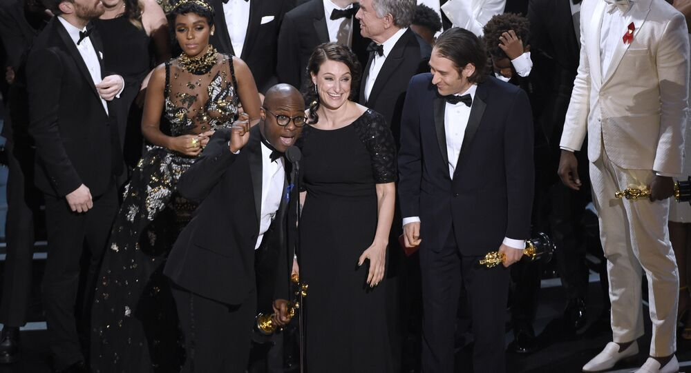 Barry Jenkins, foreground left, and the cast accept the award for best picture for Moonlight at the Oscars on Sunday, Feb. 26, 2017, at the Dolby Theatre in Los Angeles.