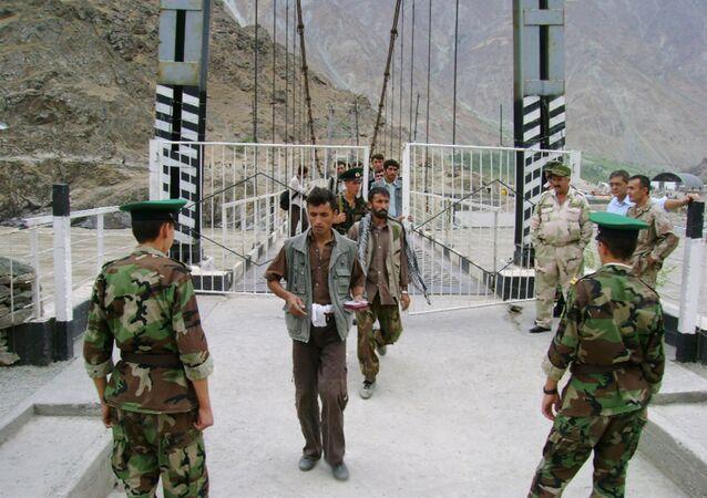 Tajik border guards checking identification documents of people crossing the Tajik-Afghan border on a bridge across the Panj River outside the city of Panj