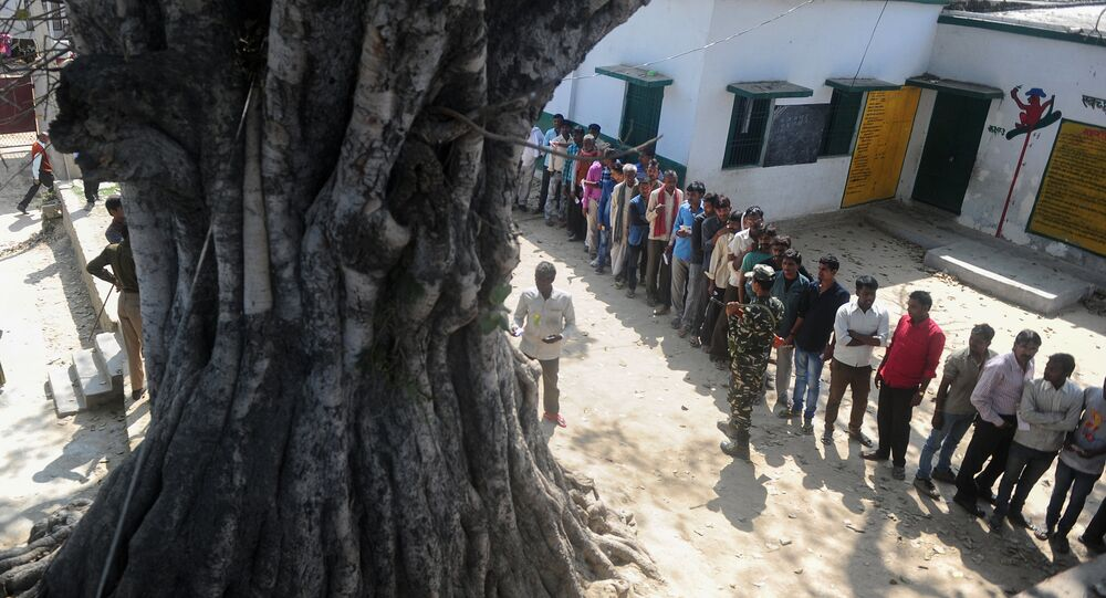 Indian voters wait in a queue for their turn to vote at a polling station in the Naini area on the outskirts of Allahabad during the fourth phase of Uttar Pradesh state assembly elections on February 23, 2017
