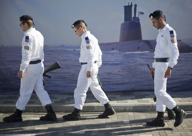 Israeli naval soldiers honor guard walks past a poster of a submarine as they wait for the arrival of a new navy submarine Rahav in the military port in Haifa, Israel, Tuesday, Jan. 12, 2016.