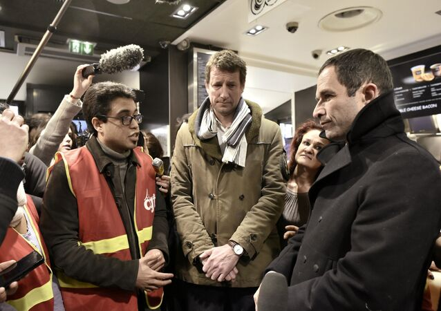 French presidential election candidate for the left-wing French Socialist (PS) party Benoit Hamon (R) talks with an unionist of the General Confederation of Labour (CGT) next to former presidential candidate for the Green Party Europe-Ecologie-Les Verts (EELV) Yannick Jadot (C) during a visit at a fast-food on February 27, 2017 in Paris