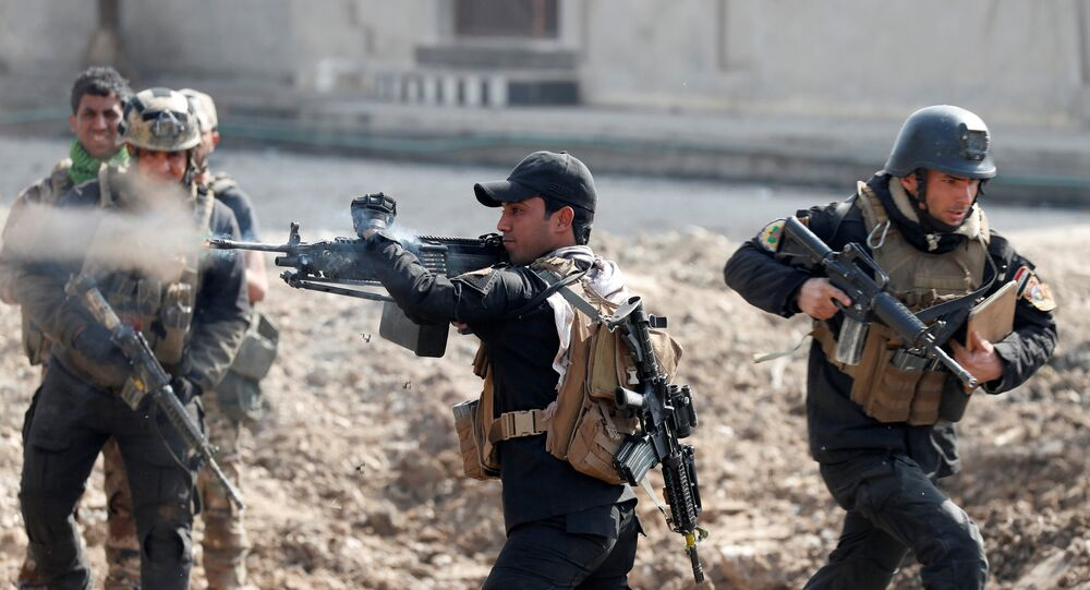 An Iraqi special forces soldier fires as other soldiers runs across a street during a battle in Mosul, Iraq March 1, 2017