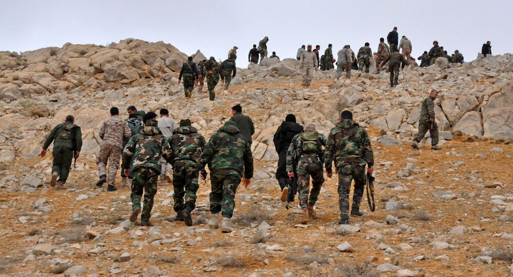 Syrian regime fighters take position as they advance to retake the ancient city of Palmyra, from Islamic State (IS) group fighters on March 2, 2017