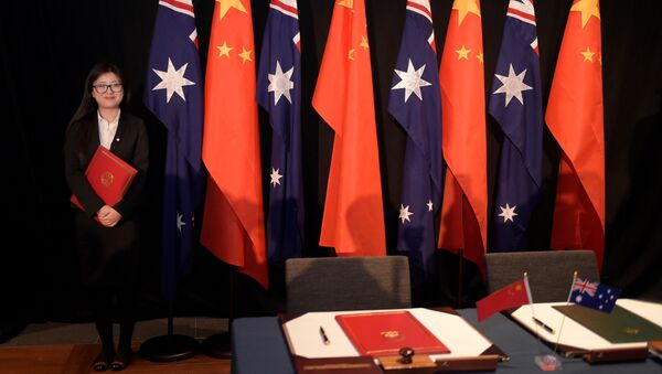 A woman holding a copy of the free trade agreement (FTA) stands next to national flags of China and Australia (File) - Sputnik International
