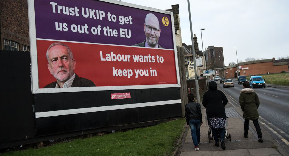 A family group walk past a UK Independence Party (UKIP) campaign poster for their candidate UKIP Leader Paul Nuttall following the result of the by-election for the Stoke-on-Trent Central constituency in Stoke-on-Trent, central England on February 24, 2017 which returned a victory for the Labour Party candidate
