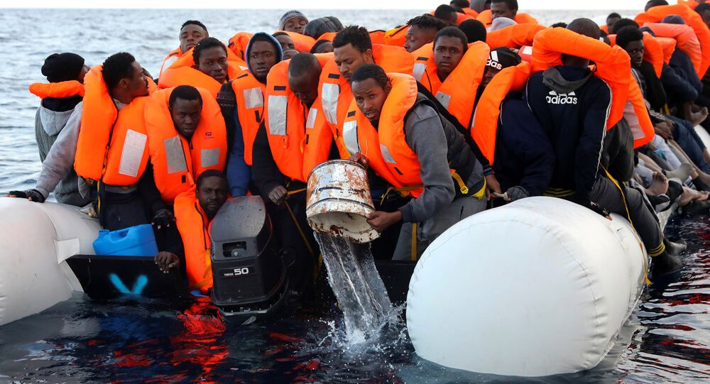 Migrants are seen aboard an overcrowded raft