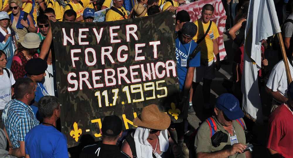 Bosnian protesters hold a banner reading 'never forget Srebrenica' during the Srebrenica Peace March near the city center of Srebrenica on July 10, 2015