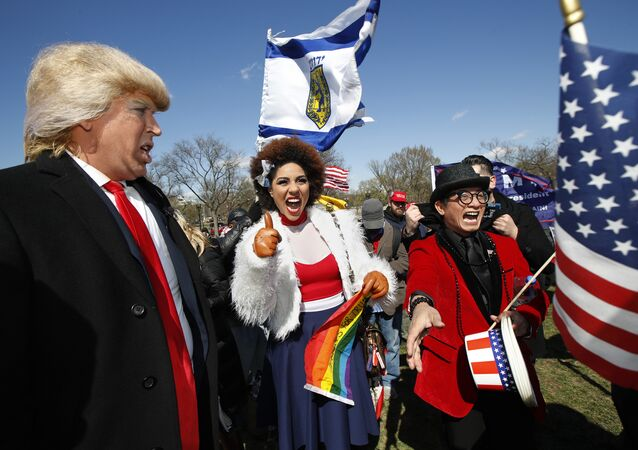 Supporters of President Donald Trump, from left, comedian Dustin Gold from Nashville Tenn., singer Joy Villa and fashion designer Andre Soriano, cheer during a rally organized by the North Carolina-based group Gays for Trump, at the National Mall near the Washington Monument in Washington, Saturday, March 4, 2017. The speakers at the rally talked about immigration, gay rights, and several other issues and later marched from the National Mall to the White House.