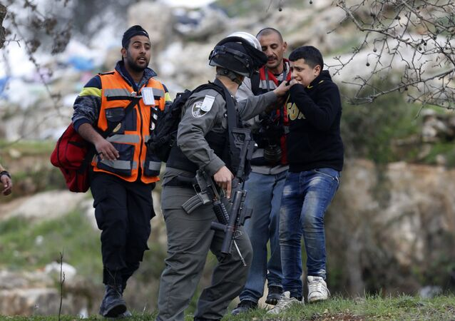 An Israeli border policeman arrests a young boy during clashes, following a protest over the death of Palestinian militant Basil al-Araj by Israeli forces early Monday, in front of the Israeli Ofer prison, near the West Bank city of Ramallah, Tuesday, March 7, 2017
