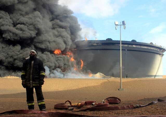 A Libyan fireman stands in front of smoke and flames rising from an oil storage tank at an oil facility in northern Libya's Ras Lanouf region on January 23, 2016, after it was set ablaze earlier in the week following attacks launched by Islamic State (IS) group jihadists to seize key port terminals
