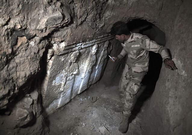 A member of the Iraqi troops stands next to archeological findings inside an underground tunnel in east Mosul on March 6, 2017