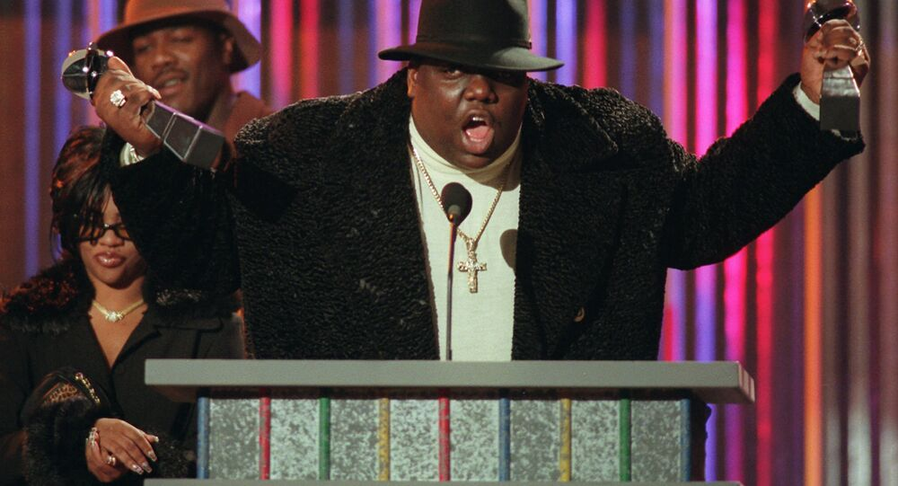 In this December 6, 1995 file photo, Notorious B.I.G., who won rap artist and rap single of the year, clutches his awards at the podium during the annual Billboard Music Awards in New York.