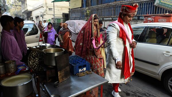 Newly married Indian man Rohit Aggarwal (R) is watched by relatives and street vendors as he leads his wife Shally Aggarwal (2R) to their home after visiting a temple in New Delhi on February 16, 2017 - Sputnik International