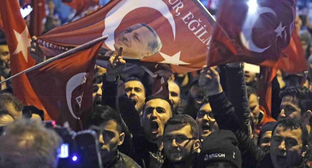 Demonstrators with banners of Turkish President Recep Tayyip Erdogan gather outsidethe Turkish consulate to welcome the Turkish Family Minister Fatma Betul Sayan Kaya, who decided to travel to Rotterdam by land after Turkish Foreign Minister Mevlut Cavusoglu's flight was barred from landing by the Dutch government, in Rotterdam, Netherlands March 11, 2017.