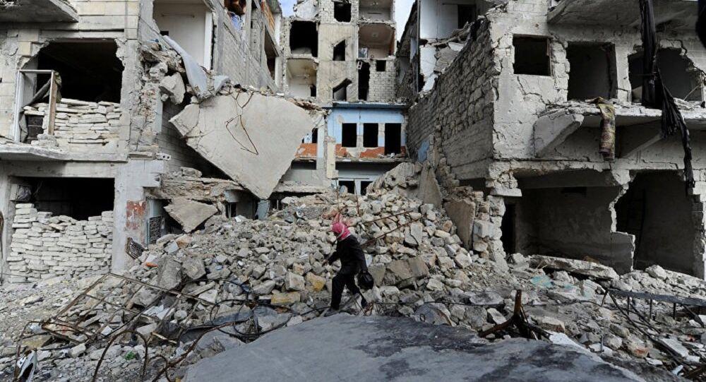 A man walks near damaged buildings in Aleppo, Syria