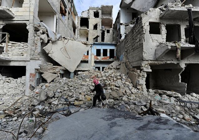A man walks near damaged buildings in Aleppo, Syria