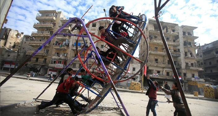 Syrian children play at the one of the street in Aleppo
