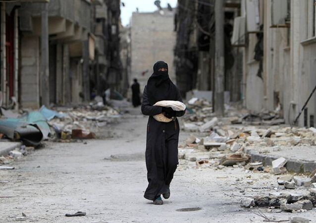 Syrian woman walks past a destroyed building in Aleppo