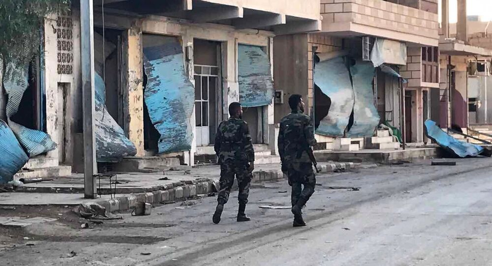 Soldiers walk past buildings destroyed during combat activities in the residential part of Ancient Palmyra in Homs Governorate, Syria