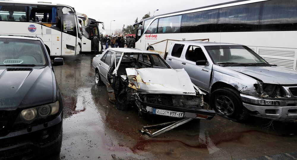 Damaged vehicles are pictured at the site of an attack by two suicide bombers in Damascus, Syria