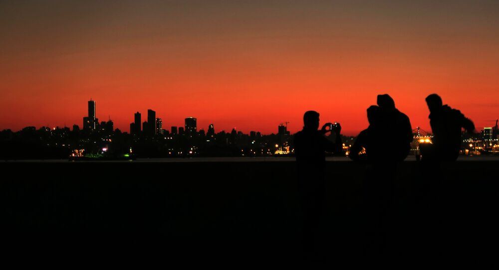Syrian refugees take a pictures as they gather on the shores of the town of Dbayeh north of Beirut as the sun sets over the Lebanese capital on February 5, 2017.