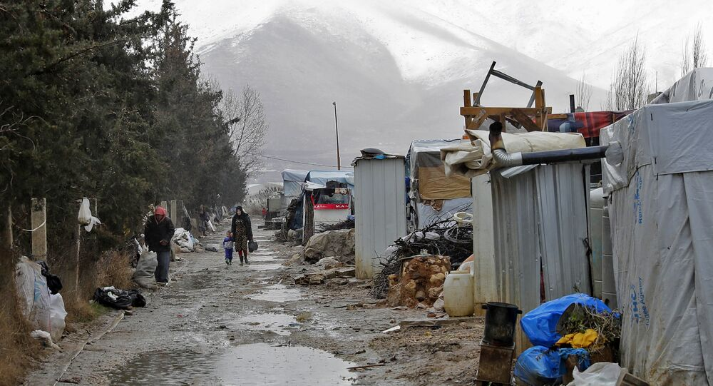 Syrian refugees walking at an unofficial refugee camp near a snow covered mountain in the village of Deir Zannoun in Lebanon's Bekaa valley.